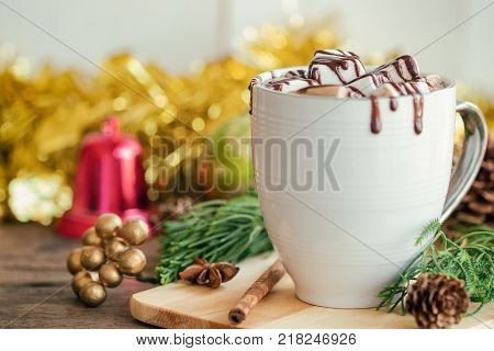 Hot chocolate in white cup topping with marshmallow and dark chocolate sauce. Homemade hot cacao or chocolate on wood table in side view copy space Christmas theme decoration background. Concept to present Christmas drink. Hot chocolate ready to served.