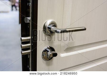 Close-up of metal bronze door handle and lock on white wooden door