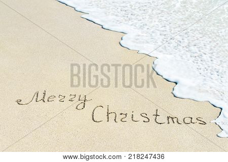 Merry Christmas caption at wet beach sand with sea wave foam - winter vacation in hot countries concept