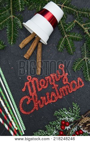 Red gleaming Merry Christmas inscription in a frame of spruce branches, red berries, straws and cinnamon sticks in a white paper cup. Close up. Top view poster