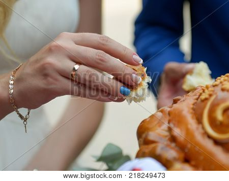 Close up hands holding piece of weding bread Russian tradition