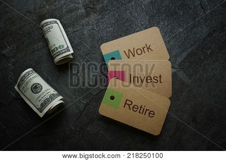 Work Invest Retirement text on paper tags with hundred dollar bills