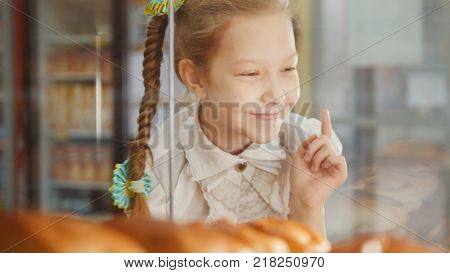 Girl with a pigtail looks at the pies in the window choosing, the girl on the other hand showcases