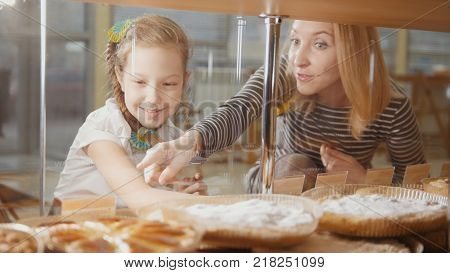 Girl with a pigtail and her mommy look at the pies in the window choosing, people on the other hand showcases