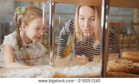 Girl with a pigtail and her mom look at the pies in the window choosing, people on the other hand showcases