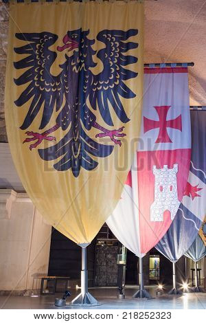 Acre Israel November 03 2017 : Knightly flags with coats of arms set in halls in the ruins of the fortress in the old city of Acre in Israel