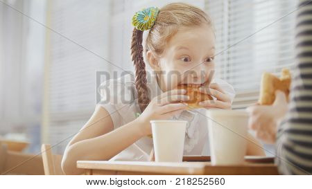 Girl with pigtail is eating sweets in the cafe, close up