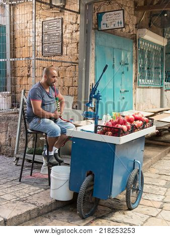 Acre Israel November 03 2017 : The seller of freshly squeezed juices sits and smokes nargila in anticipation of buyers on the market in the old city of Acre in Israel