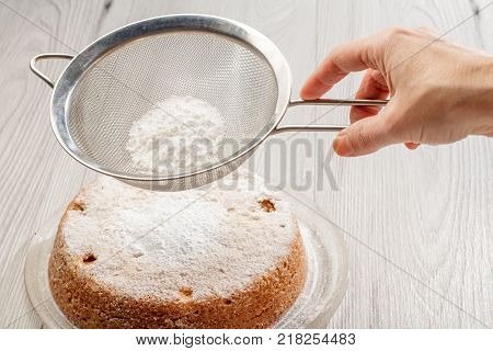 Woman's hand holding a stainless steel sieve with powdered sugar over homemade apple pie to decorate the top of the pie