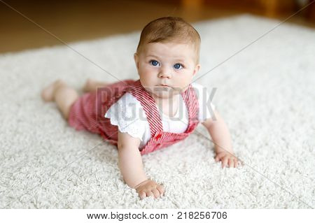 Portrait of baby girl in white sunny bedroom. Newborn child learning crawling. Nursery for children. Textile and bedding for kids. Happy child looking in a camera