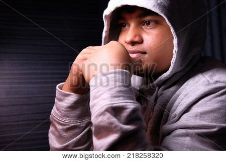 young desperate boy wearing hood in deep depression