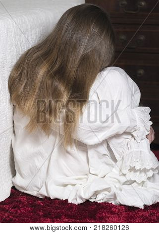 vertical image covering the Social Issues of child abuse Young unrecognisable girl is a affluent bedroom setting ashamed and scared copy space for text