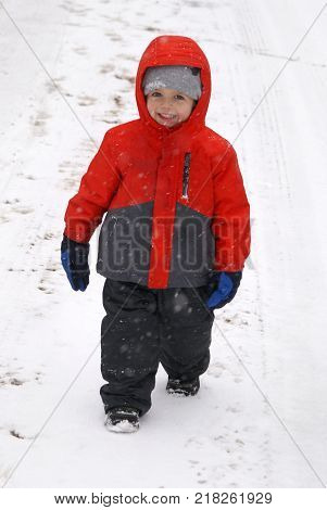 A youthful two year old boy explores his first snowfall in this winter wonderland with happy a grace on his chilled baby face.