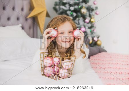 Portrait of cute happy little girl on Christmas morning in home interior. Child paying with holiday decorations making eye of pink balls while laying on bed. Horizontal color photo