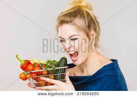 Buying good food vegetarian products. Positive funny woman holding shopping basket with green red vegetables inside recommending healthy high fibre diet lifestyle modification on grey