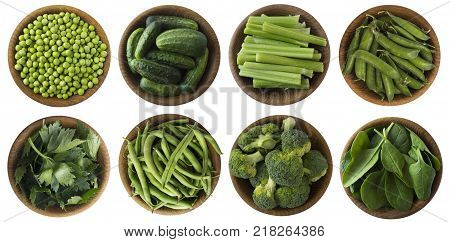 Green vegetables isolated on a white background. Brocoli green peas cucumbers and leaves parsley celery spinach in wooden bowl with copy space for text. Top view.