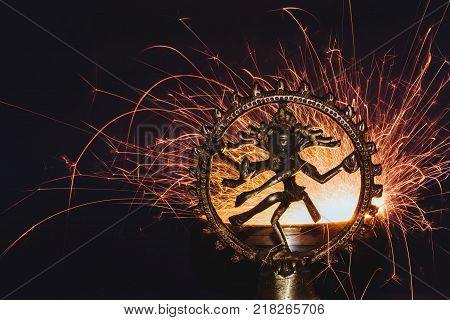 statuette of a dancing Hindu God Shiva against sparks of bengal fire