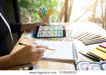 Young woman dressmaker or designer working as fashion designers and drawing sketches for clothes and choose color bar in tablet profession and job occupation Fashion Designer Stylish Concept.