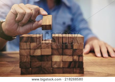 Alternative risk concept plan and strategy in business Risk To Make Business Growth Concept With Wooden Blocks hand of man has piling up a wooden block.