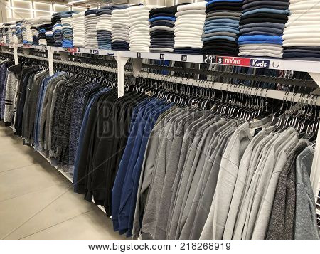 BAT YAM, ISRAEL- DECEMBER 11, 2017: Men clothes row of shirts on the racks in clothing store shopping. Wardrobe of male clothing on the hanger fabric textile