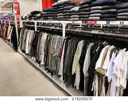 BAT YAM, ISRAEL- DECEMBER 11, 2017: Modern clothes in a shop on a hanger. Shirts and sweaters of different colors and denim for youth. Clothes of different styles on the hanger in the showroom.