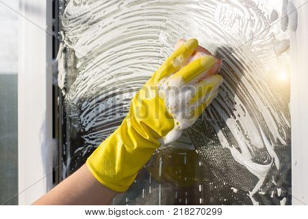 Hand cleaners in rubber glove washes a window.