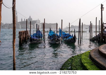 Gondolas in Venice. The gondolas are moored at the mooring posts. Venice, Italy. Gondolas without gondoliers and passengers.
