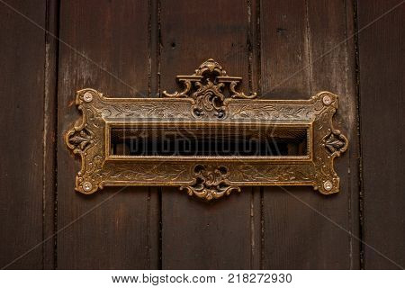 Vintage letters slot. The slot is open. The metal lining is decorated with ornate decor.