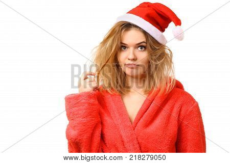 Young sleepy girl in a bathrobe in New Year's hat. Only woke up. Not combed hair. Wants to sleep. New Year. Christmas. After the holiday. Have not had enough sleep. Red Santa Claus hat. Isolated on white background
