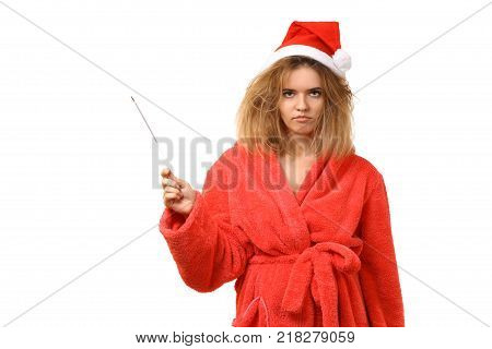 Young sleepy girl in a robe in Santa's hat with Bengal fire. Not combed hair. Wants to sleep. New Year. Christmas. After the holiday. Have not had enough sleep. Isolated on white background