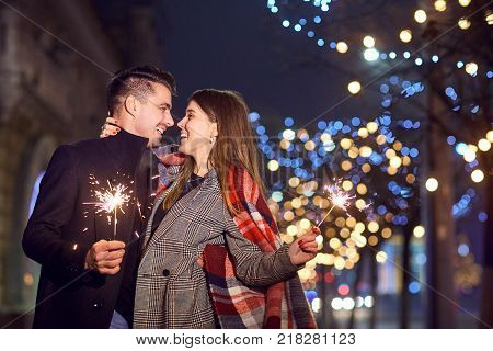 A young couple laughing with Bengal lights in the hands of a city street.