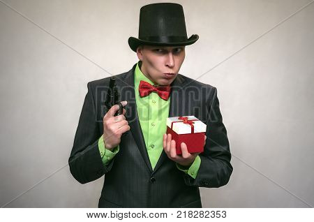 Christmas present box in the hands of confused secret detective agent isolated on white. Secret service. The spy concept.