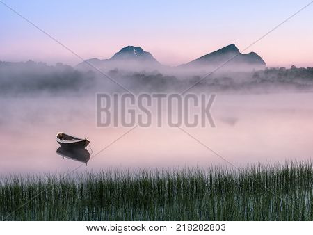 Very peaceful summer night with wooden boat and fog in Lofoten Norway