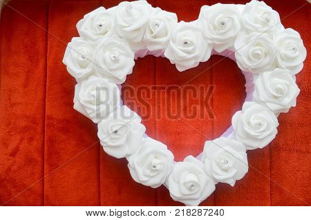 Heart from white roses with rhinestones and diamonds on a red background. Heart of flowers on a background of red carpet.