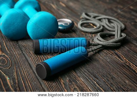 Jumping rope and dumbbells on wooden background