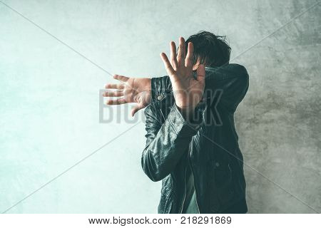 Male protecting face from violent attack. Adult caucasian man covering face and head to stop punches in a fight from attacker. Violence and crime concept.
