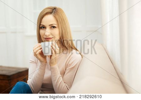 Tea time. Attractive cheerful dark-eyed slim blond woman holding a cup and wearing jeans and a beige sweater and sitting on the couch in the room