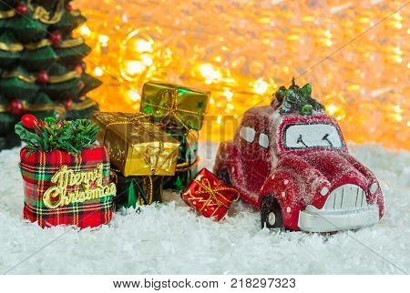 red miniature car with a Christmas tree and gifts on a white background Christmas holiday; New Year