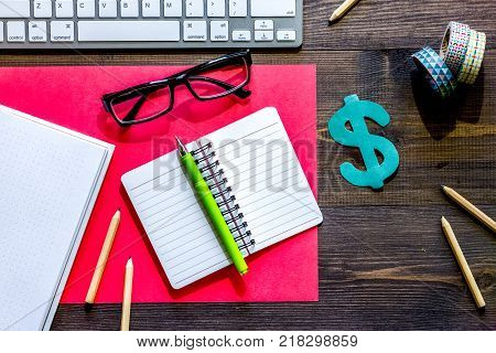 Scholarship or grant for education concept. Dollar sign, notebook and keyboard on wooden table top view.