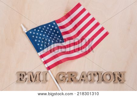 Flag of the United States word emigration in abstract letters. Wooden background