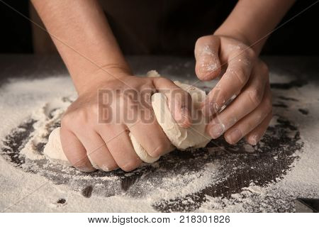 Woman kneading puff pastry on table