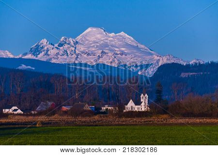 Sun setting on Mount Baker from Skagit Valley with church in foreground