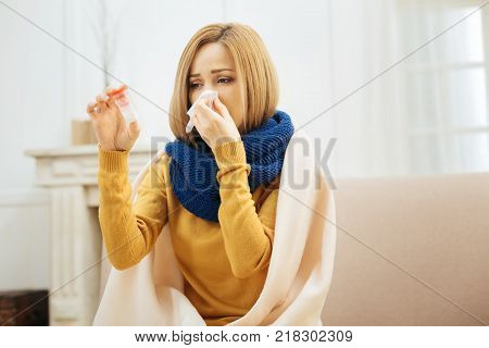 Being sick. Unhappy unwell young blond woman having fever and blowing her nose and holding medication while having a blanket on her shoulders and sitting on the couch