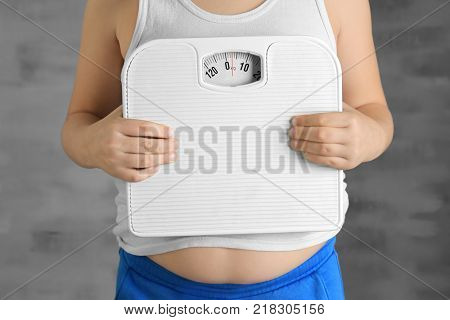 Overweight boy with scales on grey background, closeup