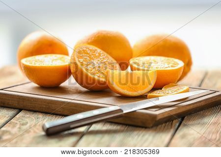 Board with fresh cut oranges and knife on table
