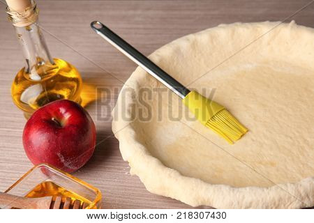 Baking pan with puff pastry and brush on table