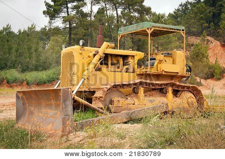 Old Rusty Bulldozer Abandoned On Middle Of Grass Against Woods