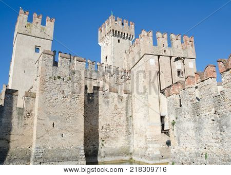 SIRMIONE ITALY. October 23rd 2017. The Scaliger Castle - a 13th Century defensive fortification - dominates the skyline of Sirmione and draws tourists into the town even in Autumn.