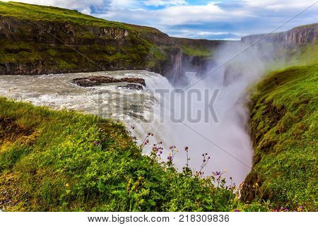 Huge masses of water crash into the abyss. Water fog fly up over falls. The most picturesque waterfall in Iceland - Gullfoss. The concept of extreme and phototour