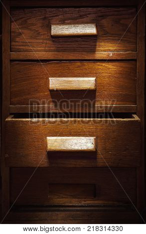 Closeup view of old wooden closet with four drawers one is opened.